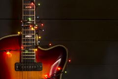 Old electric guitar with a lighted garland on a dark background. Greeting, Christmas, New Year greeting card. Copy space. Old electric guitar with a lighted stock photos