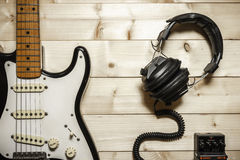 Old Electric Guitar on the Wood Background. With headphones, and audio processing effect Royalty Free Stock Photography