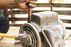 Old electric motor  and man working equipment repair on wooden floor background.Background mechanic or equipment Royalty Free Stock Images