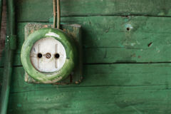 Old electric outlet on green wooden wall Stock Image