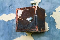 The old electric shield hangs on the exfoliating wall of the house, a rusty metal box hanging on the wall royalty free stock images