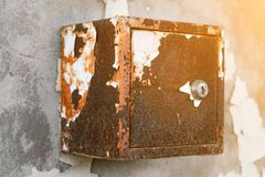 The old electric shield hangs on the exfoliating wall of the house, a rusty metal box hanging on the wall stock photo
