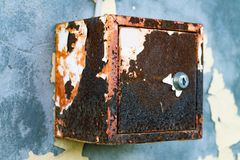The old electric shield hangs on the exfoliating wall of the house, a rusty metal box hanging on the wall stock image