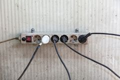 An old electric splitter with sockets and wires with plugs attached to different sides with a broken red switch. Concept of a stock image