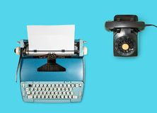 Old electric typewriter and phone on plain background Royalty Free Stock Image