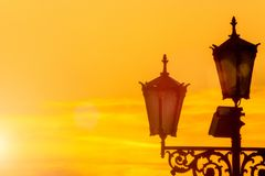 Old electrical street light on yellow sunrise sky background. Sun glare. Space for text Royalty Free Stock Image