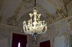 Old, elegant chandelier. Classic crystal chandelier hanging from decorated ceiling Royalty Free Stock Photography
