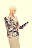 An old elegant lady with tablet. Stock Photos