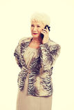 An old elegant lady using mobile phone. Stock Photography