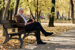 Old elegant man reading a book outside Royalty Free Stock Image