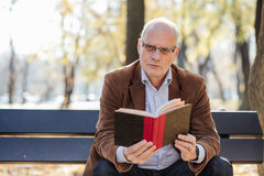 Old elegant man reading a book outside Royalty Free Stock Photos