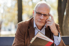 Old elegant man reading a book outside Stock Image