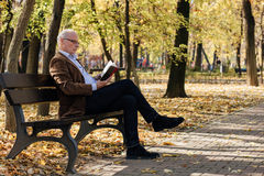 Old elegant man reading a book outside Stock Images