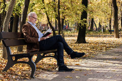 Old elegant man reading a book outside Stock Photos