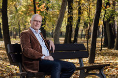 Old elegant man sitting on bench outside Stock Images