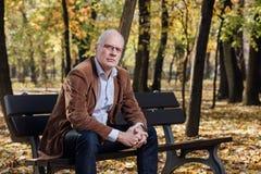 Old elegant man sitting on bench outside Stock Photo