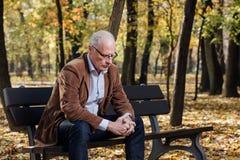 Old elegant man sitting on bench outside Stock Image