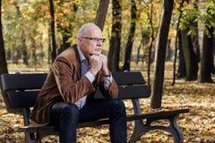 Old elegant man sitting on bench outside Stock Photos