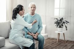 Old embarrassing man sitting and having medical examination. Preventive examination. Old pleasant embarrassing men sitting in the white room near the nurse Stock Photo