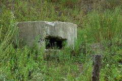 The old embrasure of the military pillbox in the grass behind the barbed wire. Concrete building with embrasure in the grass royalty free stock images