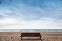 Old empty bench stands on sandy beach Stock Photo