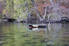 Old empty boat in a colored lake, text space. Weathered boat in green colored water, background Royalty Free Stock Image