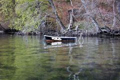 Old empty boat in a colored lake, text space. Weathered boat in green colored water, background Stock Photography