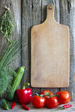 Old empty cutting board and vegetables Stock Image