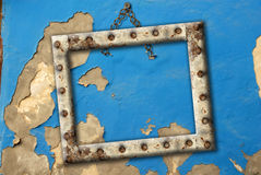 Old empty frame hanging on a broken wall blue. Old metal frame hanging on a broken wall Royalty Free Stock Image