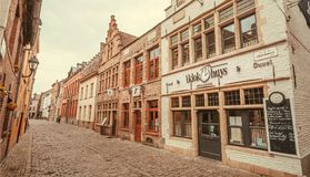 Old empty streets with stores, brick house, cobblestones on stock images