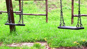 Old empty swings with chains swaying at playground for child, moved from wind stock footage