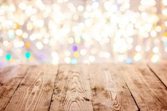 Old empty table with christmas lights in the background Stock Images
