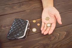 Old empty wallet and coins in the hands .Vintage empty purse and coins in hands of women . Poverty concept. Bankruptcy royalty free stock images