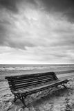 Old empty wooden bench on sandy beach Royalty Free Stock Images