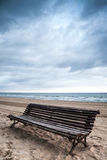Old empty wooden bench stands on sandy beach Royalty Free Stock Photography