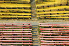 Old empty wooden benches at abandoned rural stadium Royalty Free Stock Images