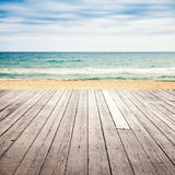 Old empty wooden pier perspective on sandy beach. Old empty wooden pier perspective with sandy beach and sea on a background Royalty Free Stock Image