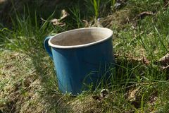 Old enamel metal battered mug grass garden stock photos
