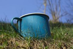 Old enamel metal battered mug grass garden with sky background royalty free stock photos