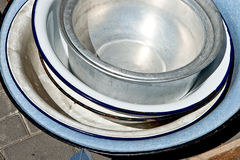 Old enameled and aluminium basins of the different sizes Stock Images