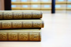 Old encyclopedia in three parts on the desk in the library. With blurry library catalog in the background stock image