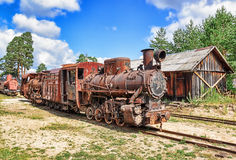 Old engine. The old rusty damaged train engine against the clear sky Stock Image