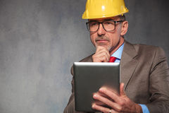 Old engineer wearing glasses and helmet while thinking Stock Photo