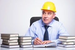 Old engineer writes at desk while pondering Royalty Free Stock Images