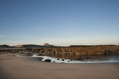 Old English Castle on a Beach. A English castle shown from a deserted beach at sunrise with rock pool just after the tide went out Stock Image