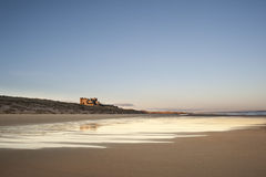 Old English Castle on the Beach. A English castle shown from a wet deserted beach at sunrise just after the tide went out Royalty Free Stock Image