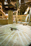 Old English flour mill. Wide angle view of the interior of an old English flour mill. The millstone dominates the lower half of the frame with the mechanism from stock images