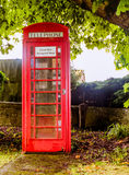 An Old English, Red Telephone Kiosk. A traditional old red English telephone kiosk situated in the heart of a village Stock Images