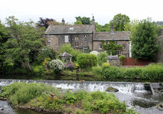 Old English Riverside Home. A quaint old English home alongside the river Aire with a man made industrial waterfall. Photo taken in Bingley, Yorkshire, England Stock Photography