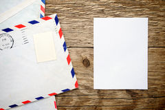 Old envelope and paper sheet. On wooden background Stock Images